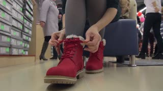Woman trying on a pair of red winter boots in a shoe store