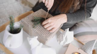Woman wraps up the gift box and decorates it, box with presents for christmas and new year, wrapping the presents, preparations for holidays