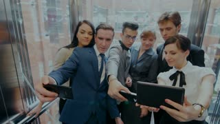 a group of businessmen in an elevator makes SELF