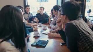 a group of young people talking in a cafe