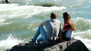 a young couple talking to the shore fast mountain river.