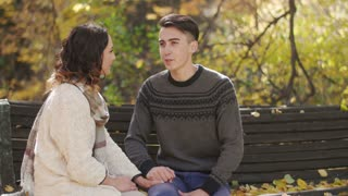 boy and girl sitting on a bench , talking