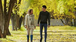 Boy and girl walk on autumn alley