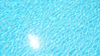 Clear, blue water in the pool. With the reflection of the sun.