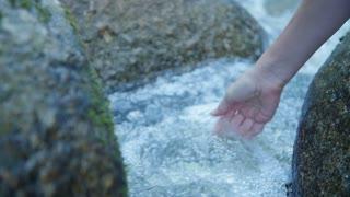 Female hand in water stream