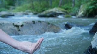 Female hand in water stream