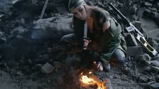 girl in military uniform, heated by the fire in the destroyed building