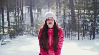 Girl throws snow up in the winter forest .