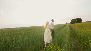 Happy couple having fun outdoors. Couple running away on the meadow.