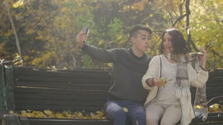 Happy couple taking selfie photos sitting in a bench autumn in a park