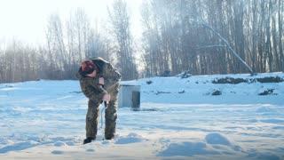 Ice fisherman drill on winter lake