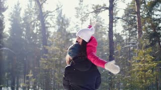 Man carries his girlfriend on his back . Winter.