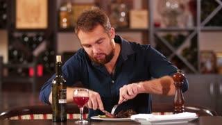 man cuts off a piece of steak close-up