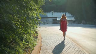Red-haired girl walking through the city at sunset