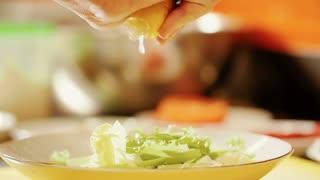 Squeezing lemon juice on the salad greens.