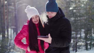 The guy with the girl look smart in the winter forest .