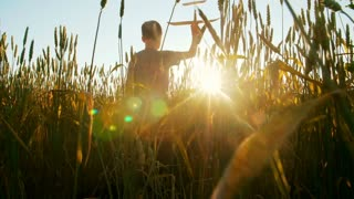 A boy at sunset, in the field, playing with an airplane