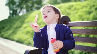 A boy in the park blowing soap bubbles.