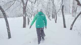A girl is walking on a snow-covered park.