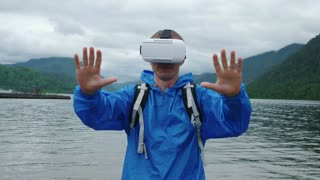 A man uses virtual reality glasses on the background of a mountain lake