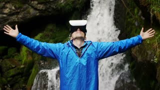 A man uses virtual reality glasses on the background of a mountain waterfall
