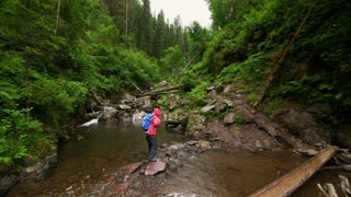 A tourist crosses a mountain stream