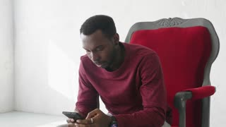 black man uses a smartphone to communicate on the Internet.