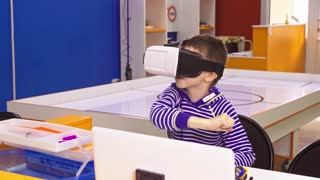 Children experiencing virtual reality. Surprised little boy looking in VR glasses.