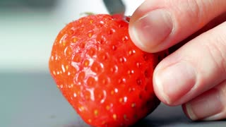 Concept of cutting strawberries with a knife in the kitchen. Close-up.