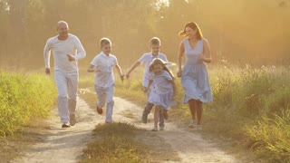 Family walking on a rural road at sunset