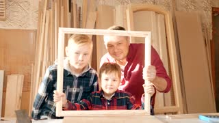 Father is a carpenter's workshop son. Friendly family indoors, funny portrait.