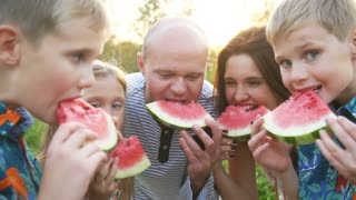 Happy family at a picnic eating watermelon
