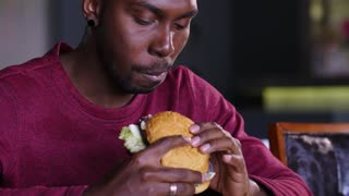 happy fat african american man eating a hamburger.