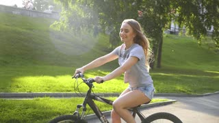 Healthy and happy cyclist woman riding fast a bicycle in a park.