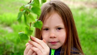 Little girl and young plant of a oak.