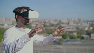 Man dressed virtual reality glasses on the city background.