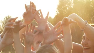 Many hands against the setting sun