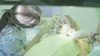 Medical office. The dentist is treating the teeth to the child.