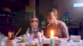 mother teaches her daughter to make a Christmas toy.