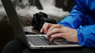Photographer working on a computer on a waterfall background.