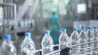 Plastic water bottles on conveyor and water bottling machine industry.