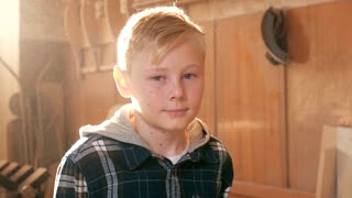 Portrait of a child in a carpentry workshop.