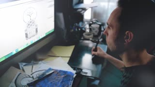 Portrait of a man. The designer draws a sketch on a graphic tablet.