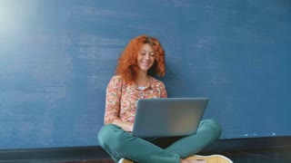 Portrait of a woman with a red hair working on a laptop.