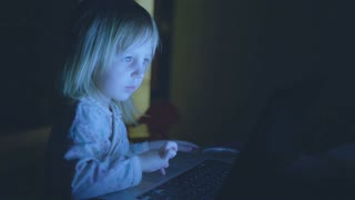 small child is playing on a computer in a dark room at home.