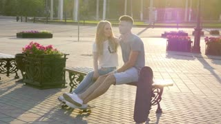 Teenage couple is posing with skateboards in the city.