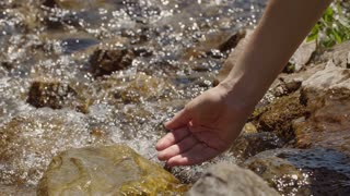 The girl draws water in a clean mountain stream