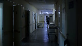 The patient walks the dark hospital corridor on crutches.