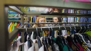 The two girls smile and choose clothes in the store. Picking clothes in the store.