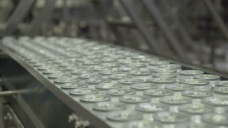 Thousands of beverage aluminum cans on conveyor line at factory.